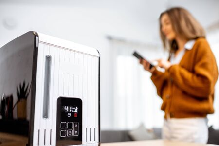 Close-up on a smart air humidifier with touch screen, woman controlling it with smart phone on the background