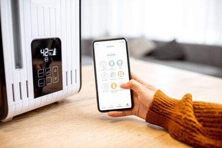 Gros plan sur un smartphone avec application d'assistant à domicile lancée, contrôlant l'humidificateur d'air à la maison