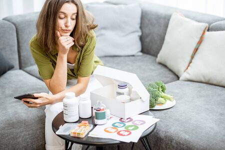 Thoughtful woman with nutritional supplements at home. Concept of individual online selection of food supplements and preventive medicine