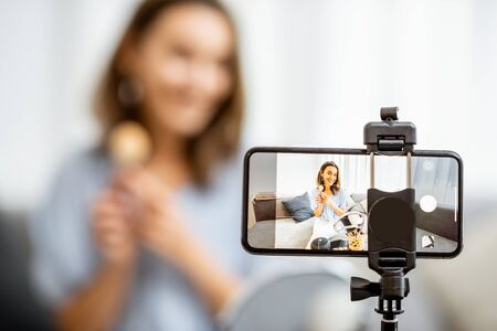 Young woman recording on a smart phone her vlog about cosmetics, showing and demonstrating makeup, close-up on phone. Influencer marketing in social media concept