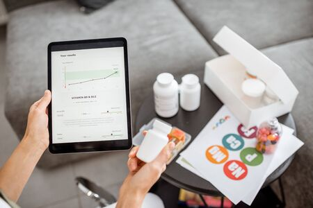 Woman checking the result of medical tests on a digital tablet, close-up with nutritional supplements on the background. Concept of individual online selection of food supplements Stock Photo