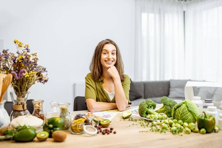 Portrait of a young cheerful woman with lots of healthy green food on the table. Concept of vegetarianism and well-being