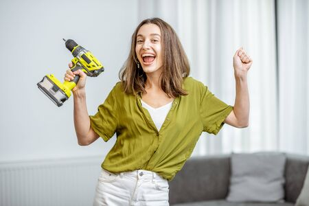 Portrait of a young and happy handywoman with cordless screwdriver at home. Concept of an easy household work with modern working tools