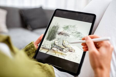 Artist or designer making landscape design, drawing on a digital tablet with pencil, close-up on a screen. Designing on a digital touchpad concept Stock Photo