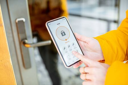 Locking smartlock on the entrance door using a smart phone remotely. Concept of using smart electronic locks with keyless access