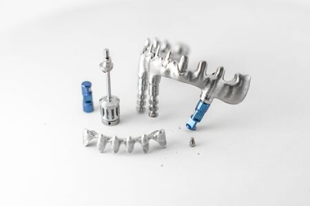 Close-up studio shot on milled metal frame for dental implants on the white background. Concept of new technologies in dental prosthetics 写真素材