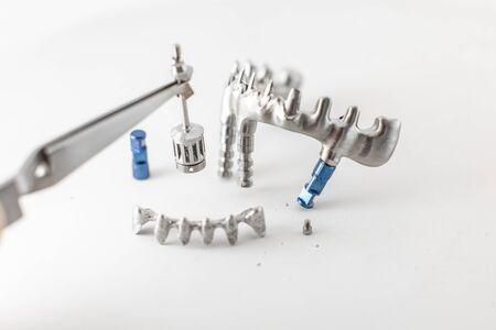 Close-up studio shot on milled metal frame for dental implants on the white background. Concept of new technologies in dental prosthetics 版權商用圖片