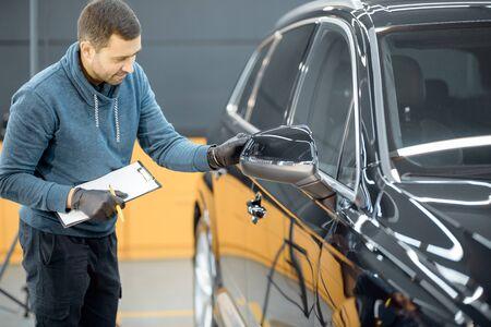 Trabajador de servicio de automóviles que examina la carrocería del vehículo en busca de arañazos y daños, y toma un automóvil para un detallado profesional de automóviles. Concepto de inspección de carrocerías profesionales