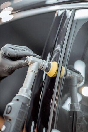 Autoservice-Mitarbeiter polieren Fahrzeugkarosserie mit Spezialwachs von Kratzern, Nahaufnahme. Professionelles Fahrzeugaufbereitungs- und Wartungskonzept