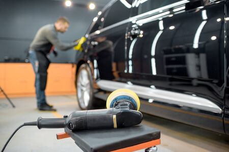 Car service worker wiping vehicle body with microfiber, examining glossy coating after the polishing procedure. Grinder on the foreground