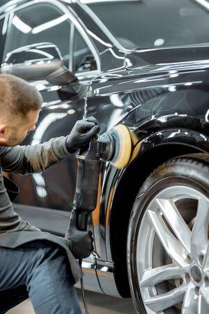 Arbeiter polieren Fahrzeugkarosserie mit Spezialschleifer und Wachs von Kratzern an der Autowerkstatt. Professionelles Fahrzeugaufbereitungs- und Wartungskonzept Standard-Bild