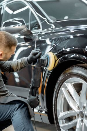 Worker polishing vehicle body with special grinder and wax from scratches at the car service station. Professional car detailing and maintenance concept Reklamní fotografie