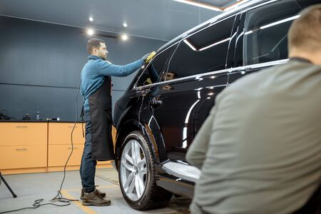 Car service workers wiping vehicle body with microfiber, examining glossy coating after the polishing procedure. Professional car detailing and maintenance concept 写真素材
