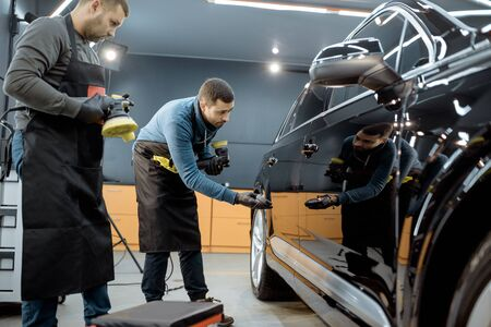 Car service workers examining glossy vehicle body coating for scratches after the polishing procedure at the service station. Car detailing concept 写真素材