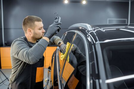 Car service worker wiping vehicle body with microfiber, examining glossy coating after the polishing procedure. Professional car detailing and maintenance concept