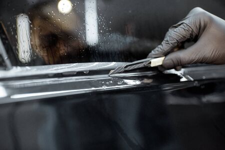 Worker trimming with cutter remains of a protective film, sticking it on a car body at the vehicle service, close-up. Concept of car body protection with special films Imagens