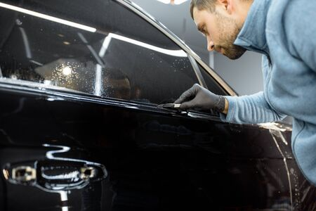 Worker trimming with cutter remains of a protective film, sticking it on a car body at the vehicle service. Concept of car body protection with special films