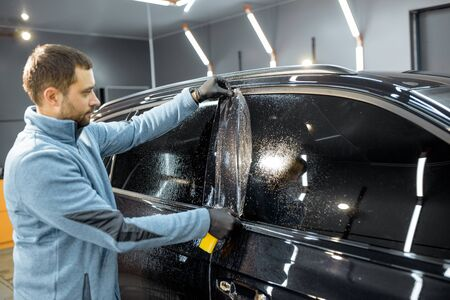 Car service worker sticking anti-gravel film on a window frame for protection at the detailing vehicle workshop. Concept of car body protection with special films