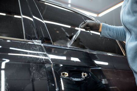Worker trimming with removing remains of a protective film, sticking it on a car body at the vehicle service, close-up. Concept of car body protection with special films