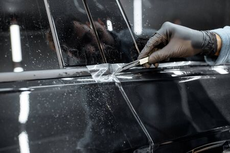 Worker trimming with cutter remains of a protective film, sticking it on a car body at the vehicle service