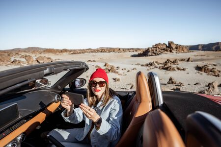 Young woman traveling by convertible car on the picturesquare road on the desert valley, photographing or vlogging on mobile phone