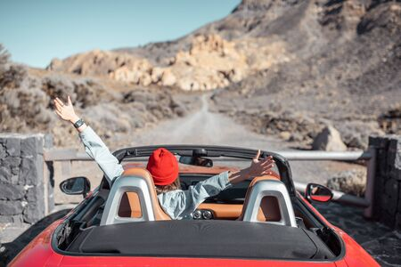 Young woman traveling by convertible car on the picturesquare road on the desert valley, rear view. Carefree lifestyle and travel concept