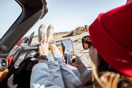 Young woman traveling by convertible car on the desert valley, pulling legs out the window and photographing with phone Archivio Fotografico