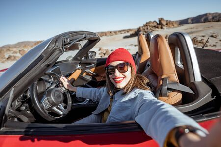 Young woman traveling by convertible car on the picturesquare desert valley, making selfie photo while driving