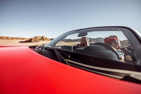 Young woman traveling by convertible car on the picturesquare desert valley, sitting at the driver seat. Front view through windshield