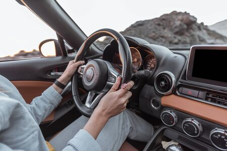 Woman driving car on the desert road, close-up view focused on the steering wheel and hands