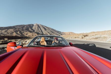 Woman traveling by convertible car on the picturesquare volcanic valley. Wide view with red car hood on the foreground