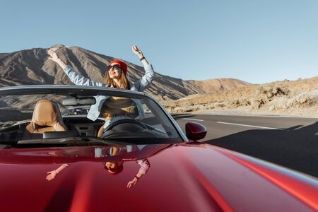 Carefree woman dressed casually in jeans and red hat enjoying road trip on the volcanic valley, raising hands from convertible car on the roadside