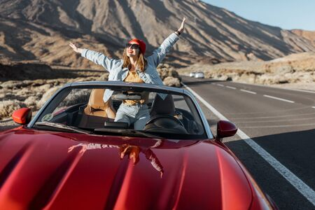 Carefree woman dressed casually in jeans and red hat enjoying road trip on the volcanic valley, raising hands from convertible car on the roadside Archivio Fotografico