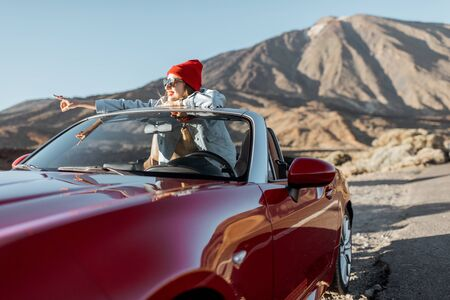 Lifestyle portrait of a young woman enjoying road trip on the desert valley, getting out the convertible car on the roadside Archivio Fotografico