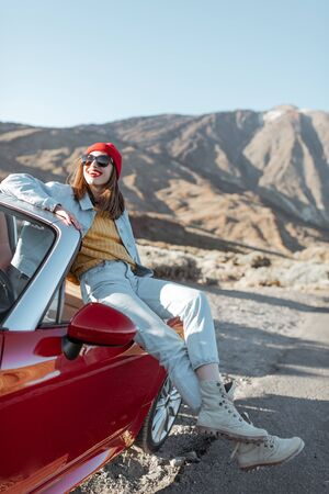 Young woman enjoying road trip on the desert valley, sitting on the convertible car on the roadside with volcano on the background Zdjęcie Seryjne