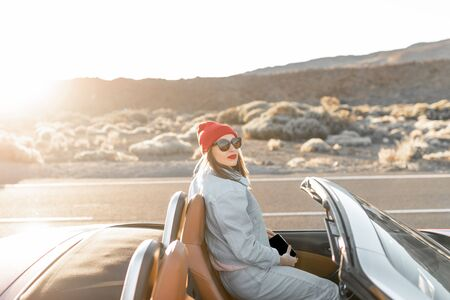 Lifestyle portrait of a young woman enjoying road trip on the desert valley, sitting on the convertible car on the roadside