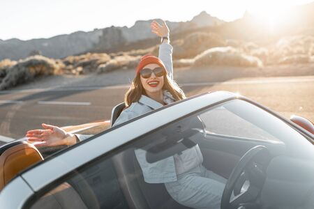 Lifestyle portrait of a playful woman having fun during a road trip, raising hands out of the convertible car while driving on the desert valley on a sunset Archivio Fotografico