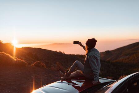 Mujer joven fotografiando con teléfono hermoso paisaje durante una puesta de sol, sentado en el capó del coche mientras viaja en lo alto de las montañas