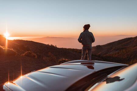 コンバーチブルスポーツカーで旅行中に美しい夕日を楽しむ女性と雲の上の道端の風景ビュー