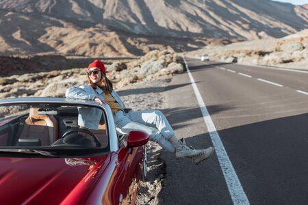 Young woman enjoying road trip on the desert valley, sitting on the convertible car on the roadside with volcano on the background