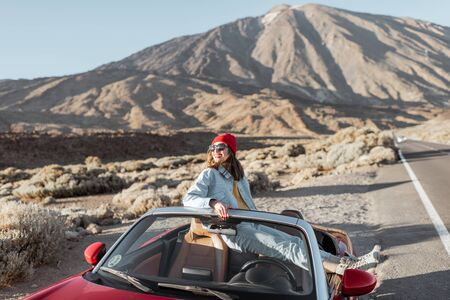 Lifestyle portrait of a young woman enjoying road trip on the desert valley, getting out of the convertible car on the roadside, pointing with hand