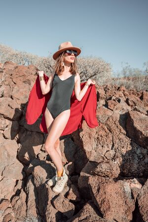 Fashion portrait of a woman dressed in swimsuit and red shirt with hat on a desert rocky landscape during sunny day
