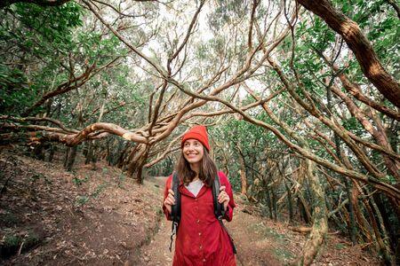 Portret van een gelukkige vrouw, nonchalant gekleed in een rood shirt en hoed, wandelend in het prachtige regenwoud tijdens een reis op het eiland Tenerife, Spanje