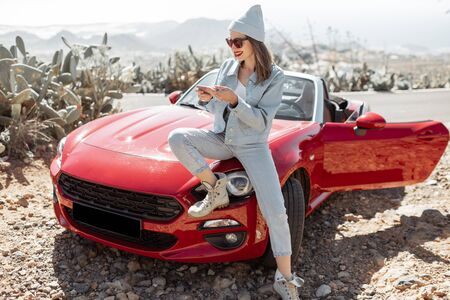 Young woman dressed casually with hat enjoying road trip on the island, standing with phone near the convertible car on the roadside