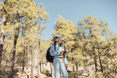 Portrait od a stylish woman enjoying beautiful landscapes on volcanic rocks in the pine woods, traveling high in the mountains on Tenerife island, Spain