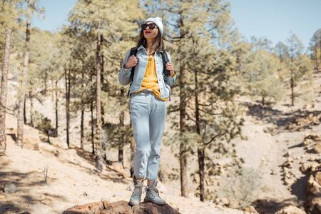 Portrait of a stylish woman enjoying beautiful landscapes on volcanic rocks in the pine woods, traveling high in the mountains on Tenerife island, Spain