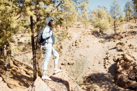 Stylish woman enjoying beautiful landscapes on volcanic rocks in the pine woods, traveling high in the mountains on Tenerife island, Spain
