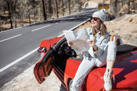 Woman enjoying road trip, sitting with map on the convertible car on the roadside in the volcanic mountain forest on Tenerife island, Spain Zdjęcie Seryjne