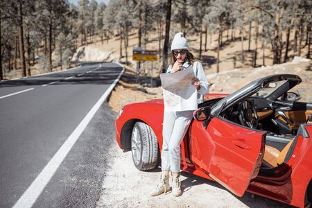Woman enjoying road trip, standing with map near convertible car on the roadside in the volcanic mountain forest on Tenerife island, Spain