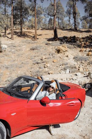 Woman enjoying road trip, sitting in the convertible car on the roadside in the volcanic mountain forest on Tenerife island, Spain Zdjęcie Seryjne